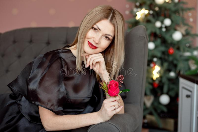 Happy New Year to you.One beautiful young woman in a black dress and bright makeup celebrating Christmas on the. Background of New Year`s garlands. New Year stock photos