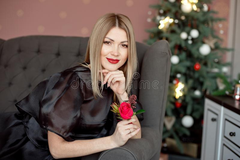 Happy New Year to you.One beautiful young woman in a black dress and bright makeup celebrating Christmas on the. Background of New Year`s garlands. New Year stock photo