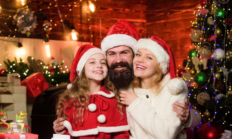 Happy New Year to you. small child and parents in santa hat. lot of xmas present boxes. Portrait loving family. Happy stock photos
