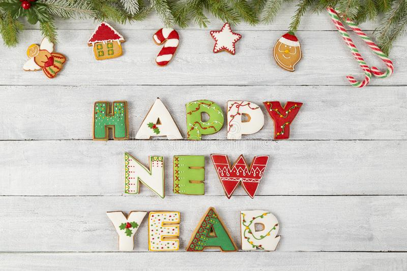 Happy New Year. Top view of nicely decorated colorful gingerbread Christmas cookies shaped like letters Happy New Year with pine branches and candy cane on royalty free stock photo