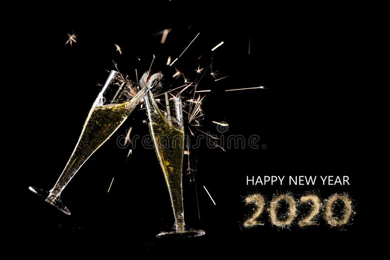 Happy new year 2020, two champagne flutes toast with splash and sparklers against a black background, party concept with text and stock photos