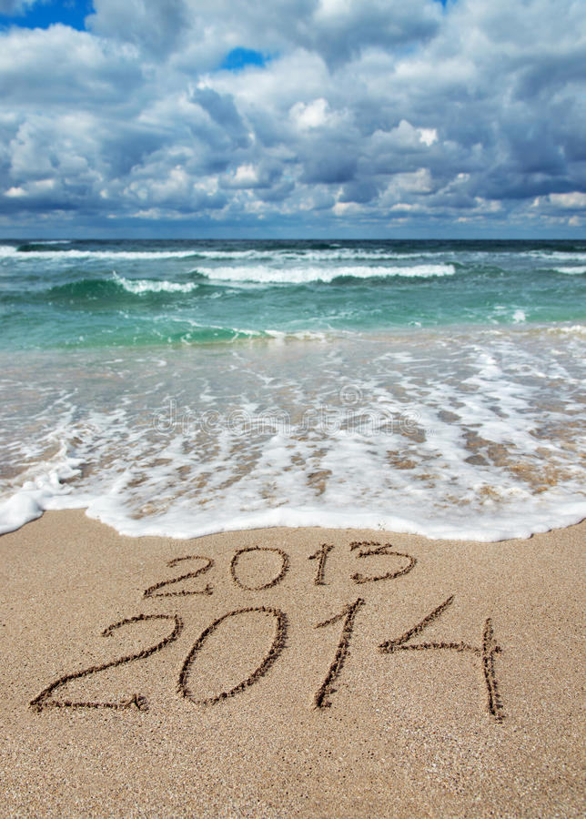 Happy New Year 2014 wash away 2013 concept on sea beach royalty free stock images