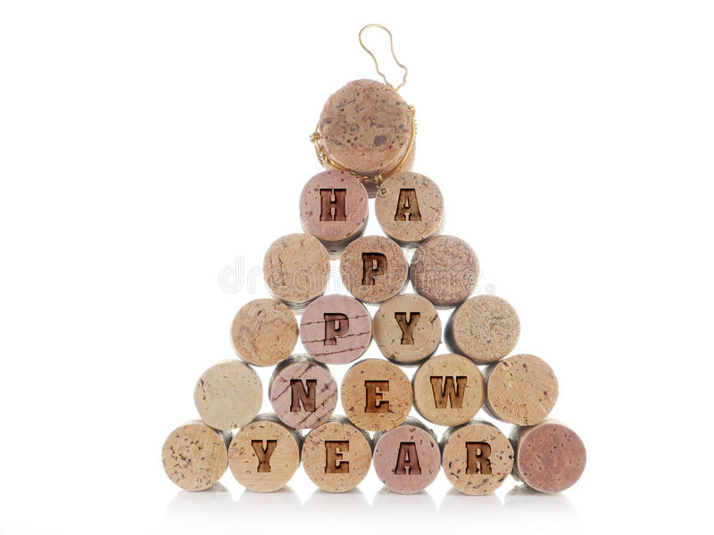Happy New Year. Wine and champagne corks arranged into pyramid with imprinted Happy New Year words over white background royalty free stock photo