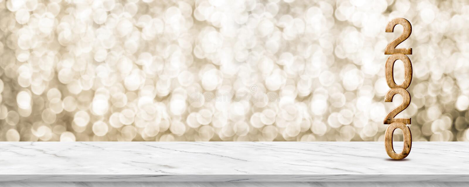 Happy New Year 2020 wood with sparkling star on marble table with gold bokeh background,Holiday festive celebration concept.Banner royalty free stock photography