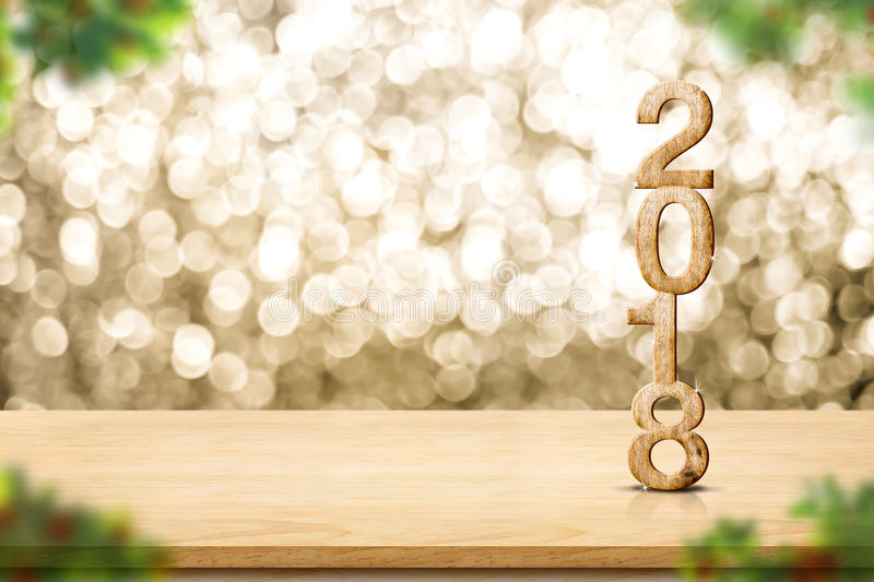 Happy new year 2018 on wood table and blur Christmas tree foreground at blur sparkling gold bokeh light wall,panoramic banner for royalty free stock photos