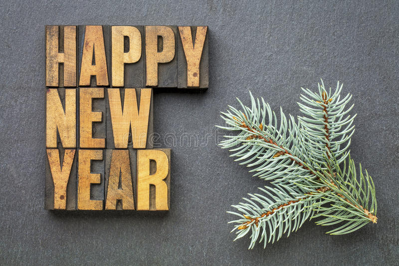 Happy New Year in wood type. Happy New Year! - word abstract in vintage letterpress wood type blocks on a slate stone with a branch of Colorado blue spruce stock photo