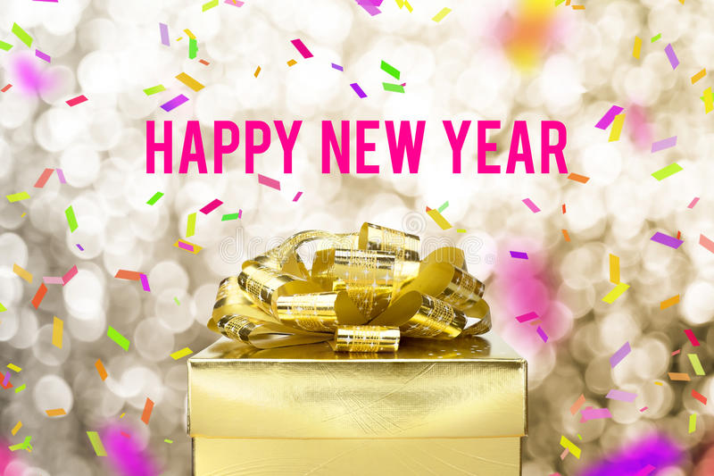 Happy new year word with Golden gift box with ribbon and colorful confetti at blur gold boekh light background,Winter holiday stock photo