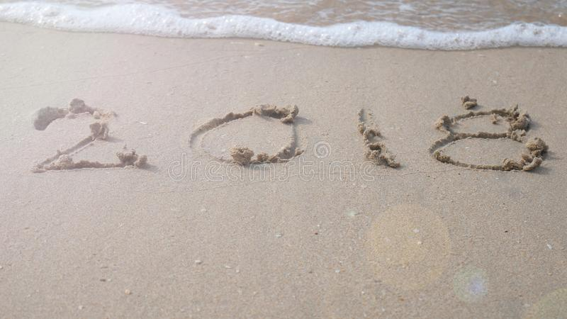 Happy new year 2018. 2018 write on sandy beach with wave splash stock photos