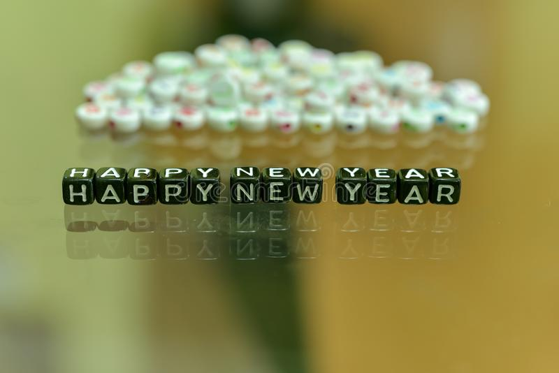 HAPPY NEW YEAR 2019 written with Acrylic Black cube with white Alphabet Beads on the Glass Background.  stock image