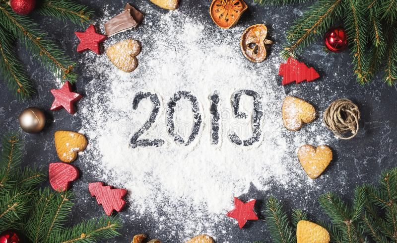 Happy New Year 2019 written on flour and Christmas Decorations Gingerbread cookies on dark stone background. New Year greeting car stock photo
