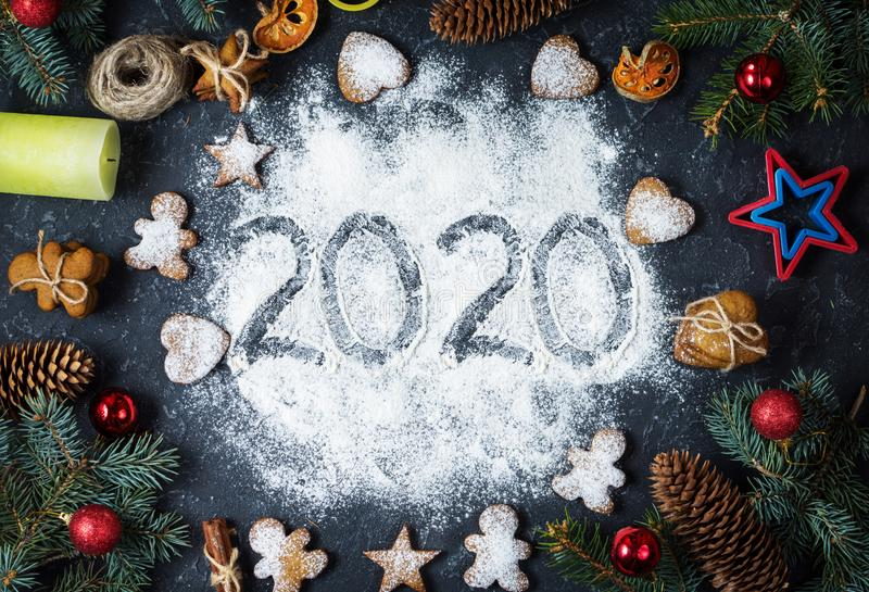 Happy New Year 2020 written on flour and Christmas Decorations Gingerbread cookies. New Year greeting card royalty free stock photography
