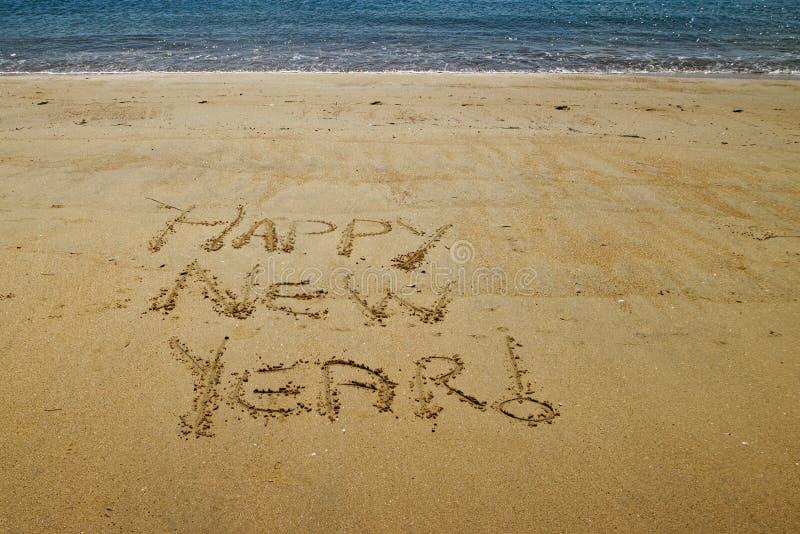 Happy New Year written in the golden sand of Little Kaiteriteri beach royalty free stock photo