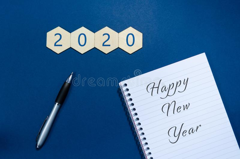 Happy New Year written on note pad in a conceptual image of the coming new year with number 2020. Over blue background royalty free stock photography