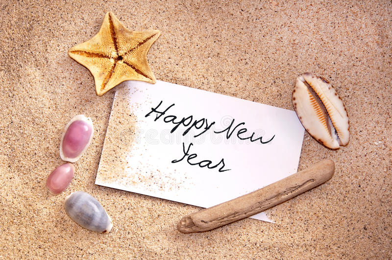 Happy new year, written on a note in the sand. With seashells royalty free stock photos