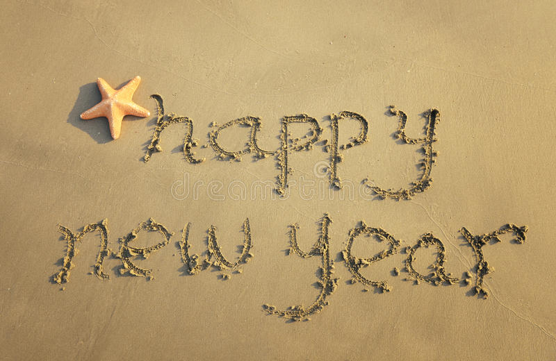 Happy new year. Written in the sand stock images