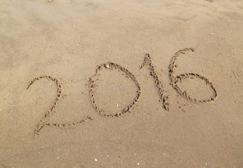 Happy new year written on sandy beach stock photography