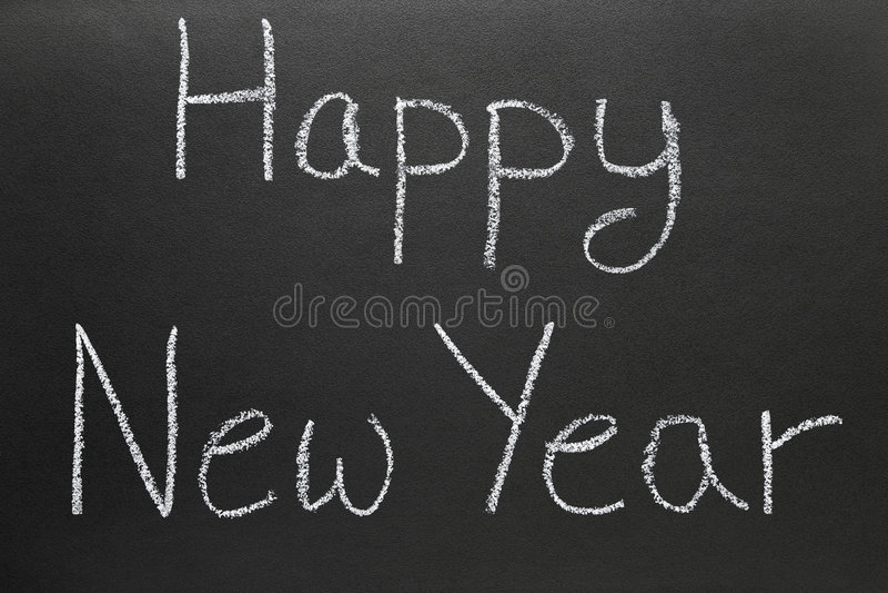 Happy New Year written on a school blackboard. Happy New Year written with chalk on a school blackboard stock image