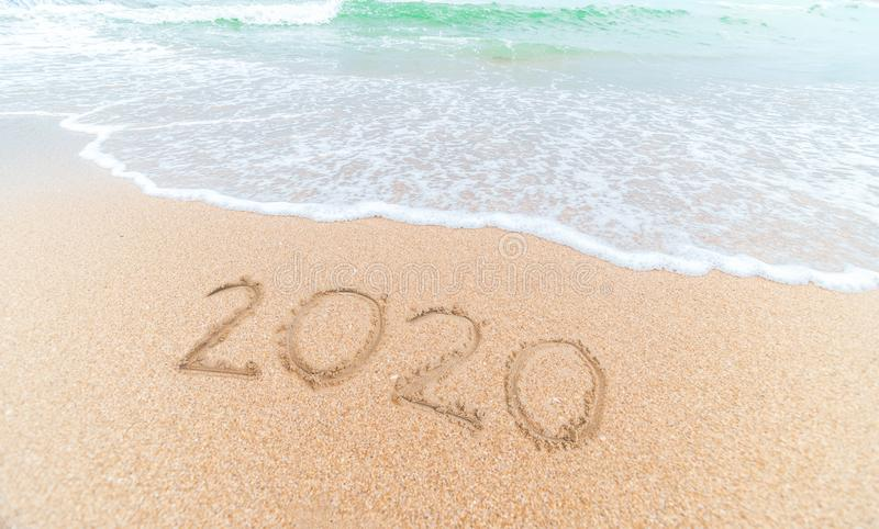 Happy New Year 2020 written on seashore sand at sunrise concept.beautiful sandy beach and soft blue ocean wave royalty free stock image