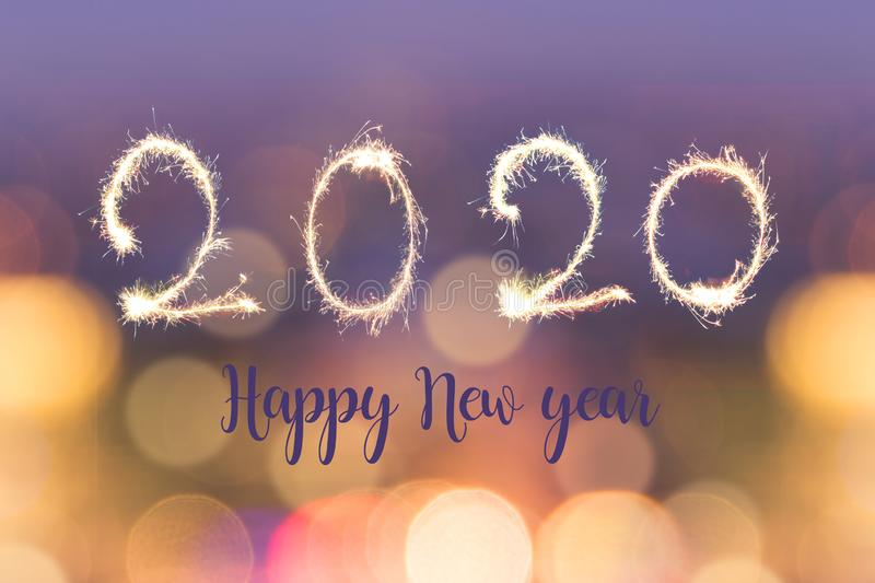 Happy new year 2020 written with sparkes on blurred bokeh lights background holiday greeting card. Happy new year 2020 written with sparkes on blurred bokeh stock image