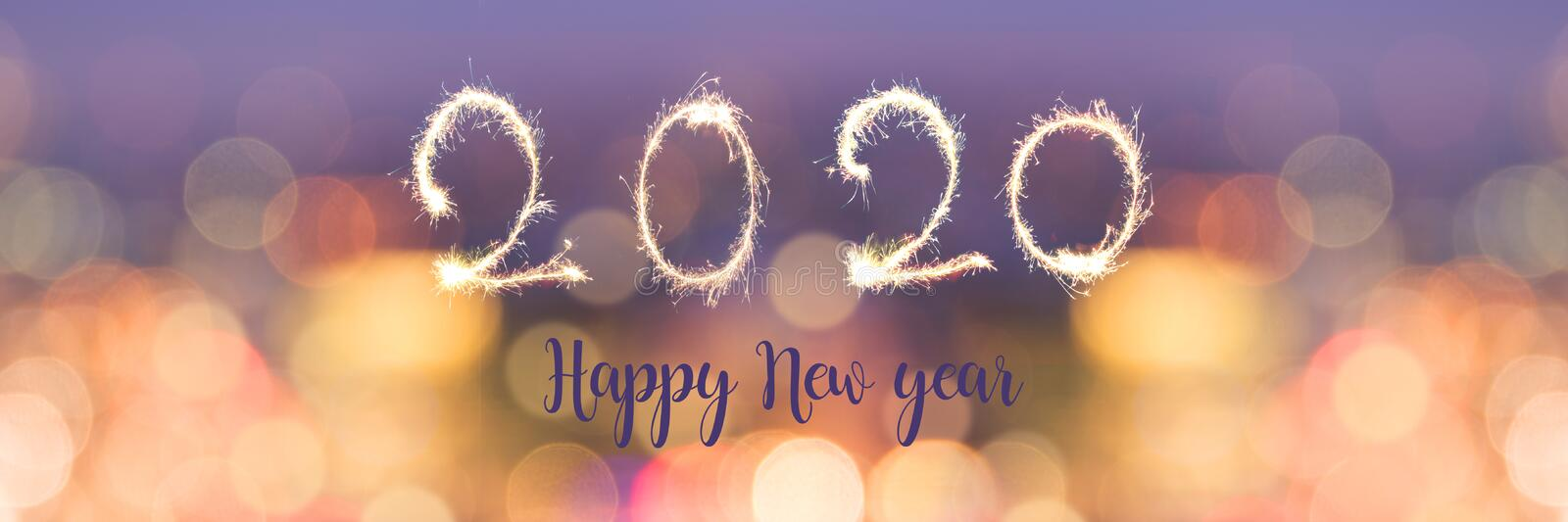 Happy new year 2020 written with sparkles on panoramic banner of blurred bokeh holiday lights stock photos
