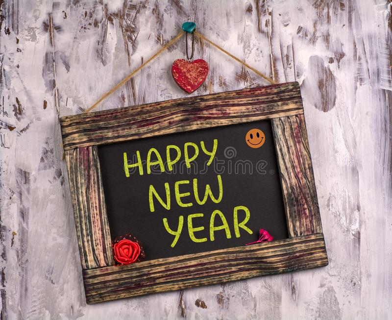 Happy new year written on Vintage sign board. Happy new year written on Vintage wooden sign board hanging on color white wood with heart and flower and smile royalty free stock photos