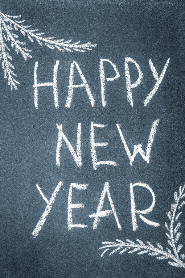 Happy New Year written in white chalk on a chalkboard royalty free stock images