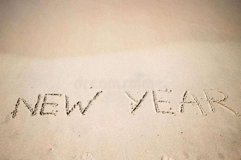 Happy New Year written in the white sand. Worlds new year written in the sand of a beach royalty free stock images