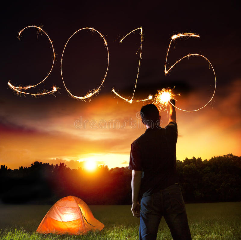Happy new year 2015. young man drawing 2015 by sparkling stick. Camping on the mountain royalty free stock photography