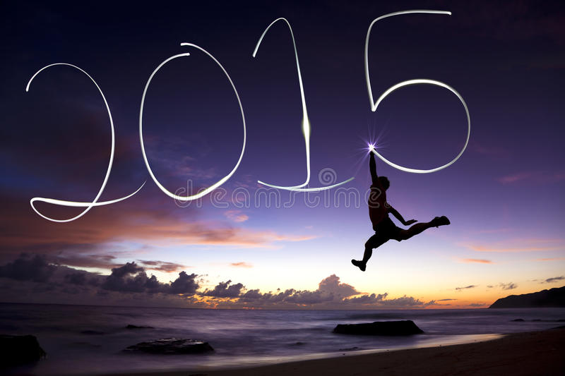 Happy new year 2015.young man jumping and drawing 2015. By flashlight background stock photo