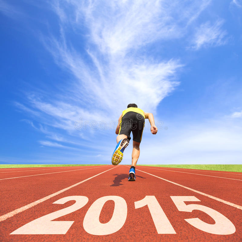 Happy new year 2015. young man running on track. With blue sky and cloud background royalty free stock photos