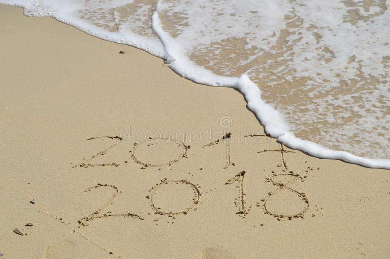 Happy New Years 2018 handwritten on sand. With a wave coming to erase 2017 stock image