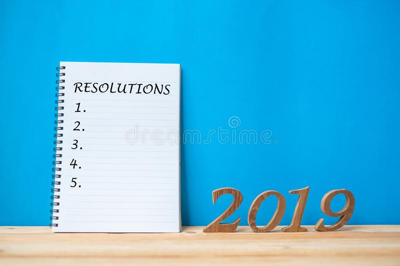 """2019 Happy New years with notebook """"Resolutions """" text and wooden number on table and copy space. New Start, Resolution, Goals and Mission Concept stock images"""