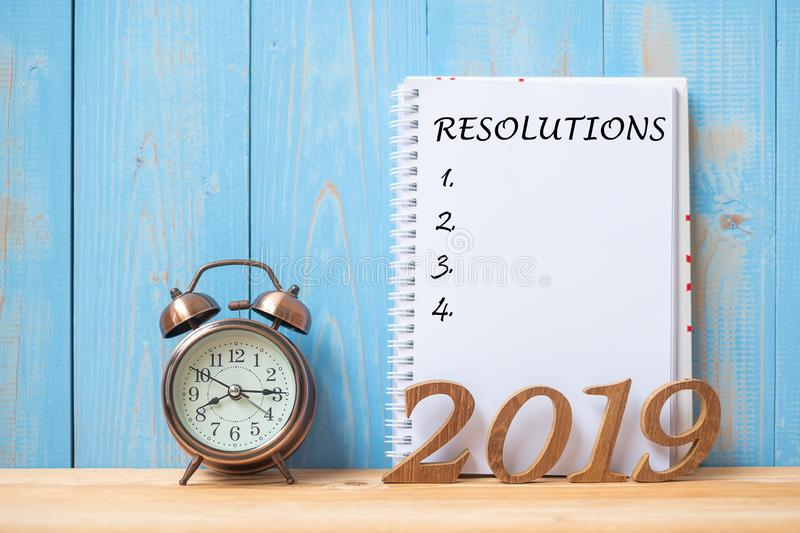 2019 Happy New years with Resolution text on notebook, retro alarm clock and wooden number on table and copy space stock photos