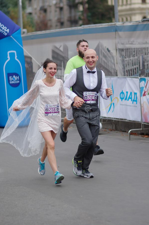 Happy newly married pair running on a city street during 5 km distance of ATB Dnipro Marathon royalty free stock photo