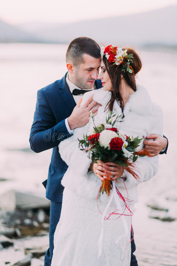 Happy newlywed bridal couple holding each other on pebble riverside with forest hills as background stock image