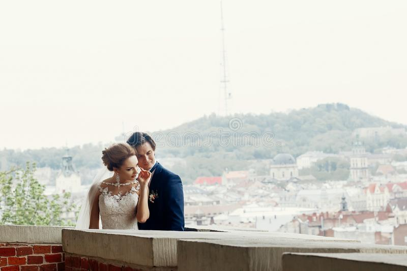 Happy newlywed couple on castle wall, cityscape and hill in the background, stylish newlyweds portrait royalty free stock photo