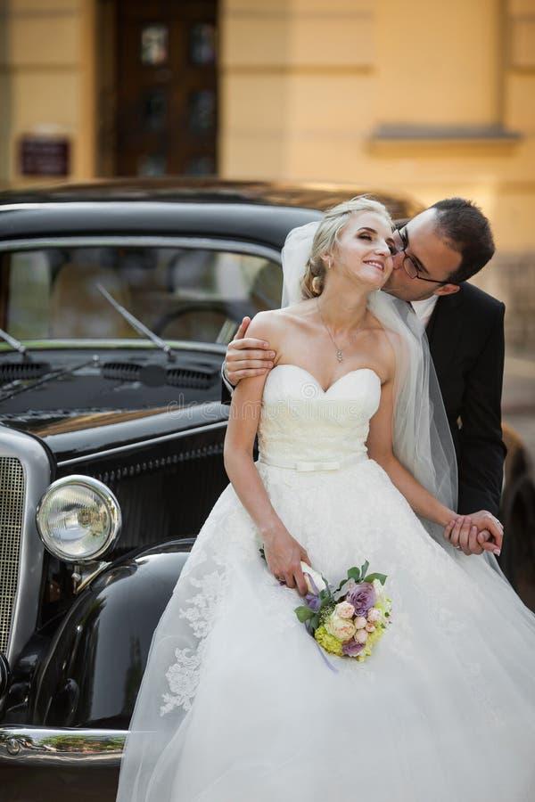 Happy newlywed couple, man and wife kissing near stylish retro c stock image