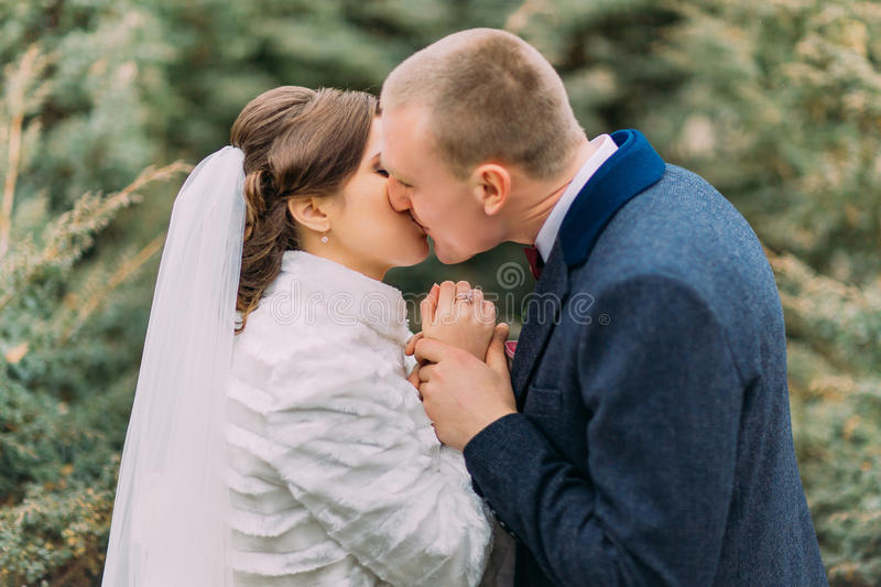 Happy newlywed pair, tender bride and gentle groom, holding hands together while kissing in green park royalty free stock photos