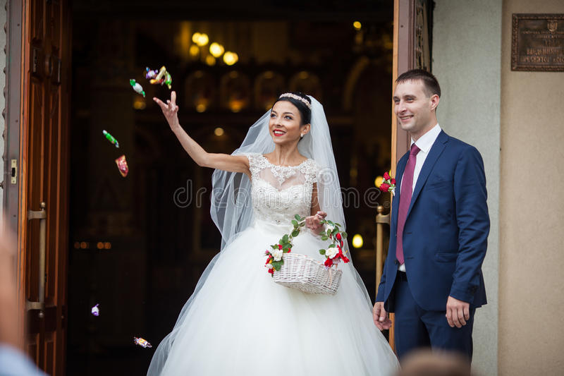 Happy newlywed romantic couple coming out of church after wedding ceremony with a candy basket royalty free stock photos