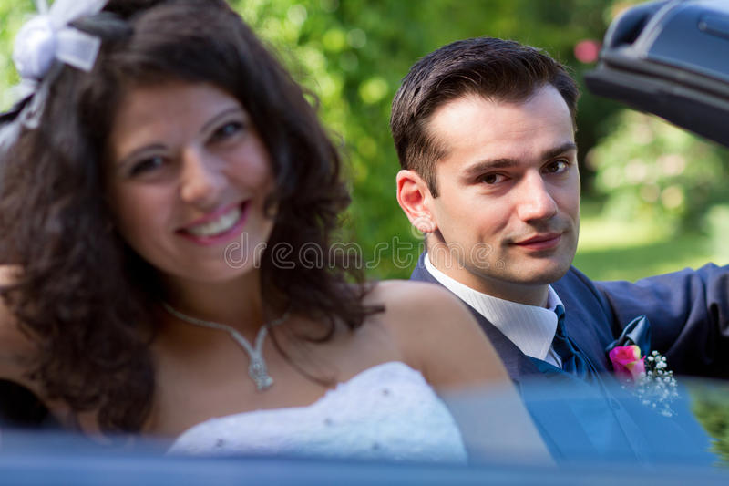 Happy newlyweds in a cabrio stock images