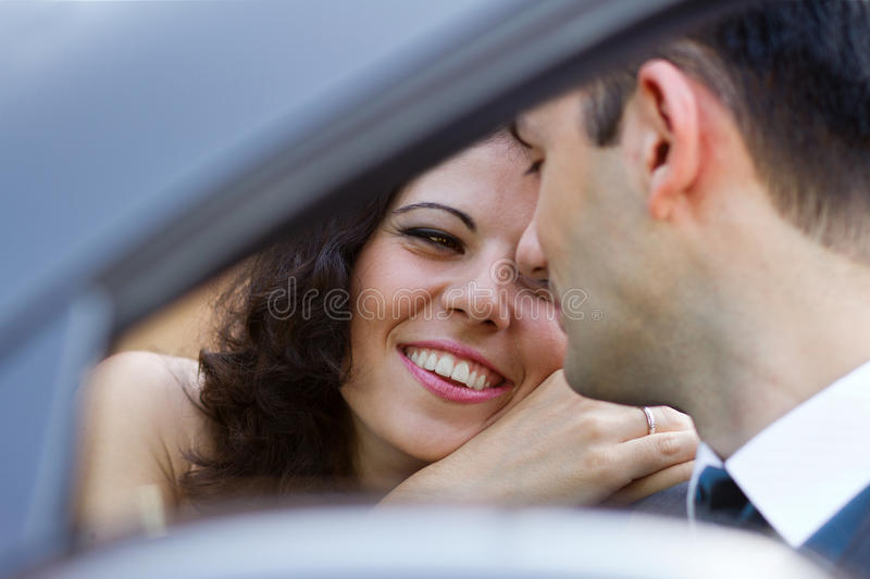 Happy newlyweds in a car royalty free stock photo