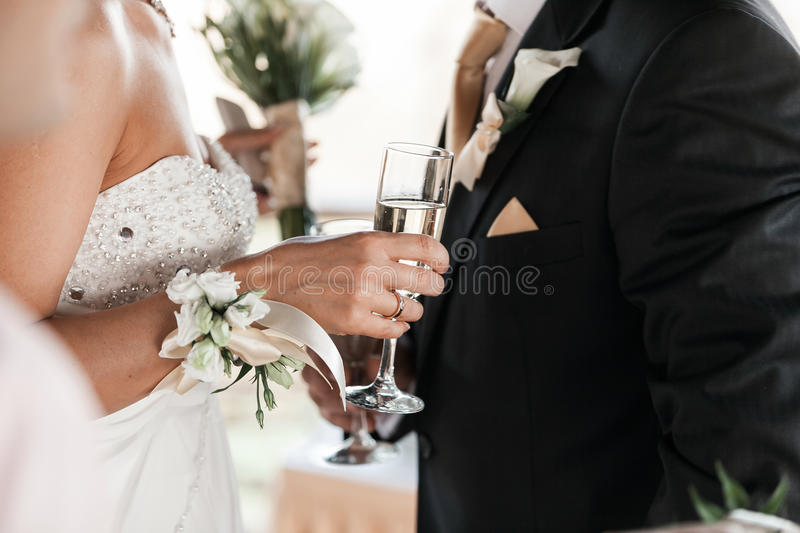 Happy newlyweds couple drink white wedding champagne wine.Decorated crystal glasses.Hands of bride and groom with gold. Ring toast with alcohol drinks.New stock photography