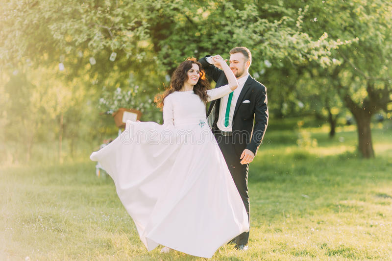 Happy newlyweds dancing on grass in park with their bicycle near the tree at background.  stock photos