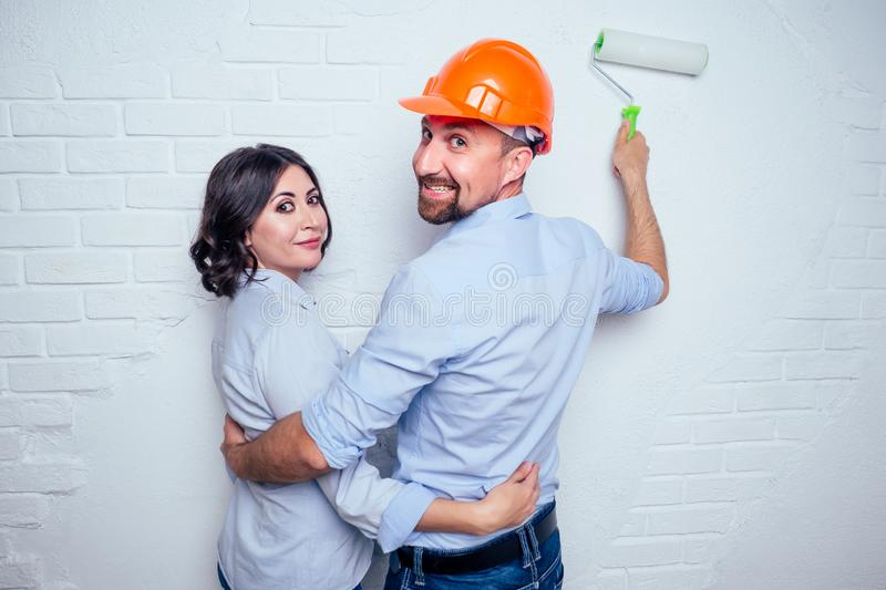 Happy newlyweds family handsome man in the construction helmet hardhat and charming woman together painting white brick royalty free stock photo