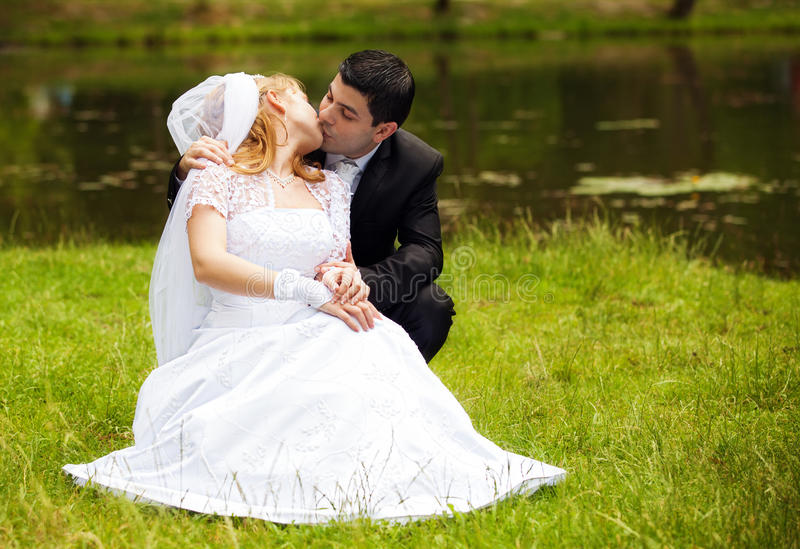 Happy Newlyweds On Grass In Park Stock Photos