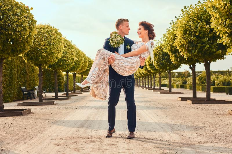 Happy newlyweds. Handsome groom holds his charming bride in her arms in the amazing garden. royalty free stock photos