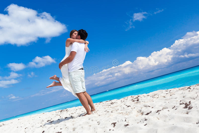 Happy newlyweds having fun on beach stock image