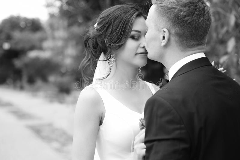 Happy newlyweds kissing outdoors, black and white. Effect stock photography