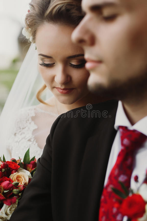 Happy newlyweds portrait, romantic couple, blonde bride with bouquet and handsome groom in stylish black suit posing outdoors, be royalty free stock photos