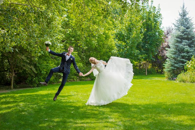 Happy newlyweds rejoice and jump on a green lawn. Wife white wedding dress, groom in a suit.  stock image